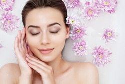 Portrait of young beauty female woman smiling with clean pure skin taking spa relaxing in bath with flowers and white soap shampoo water. Skin beauty health care concept. Body part and nature