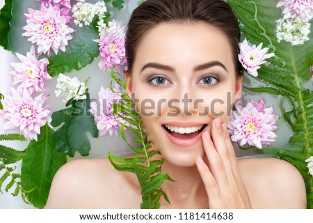 Portrait of young beauty female woman smiling with clean pure skin taking spa relaxing in bath with flowers and green leafs white soap water. Skin beauty health care concept. Body part and nature ストックフォト ©