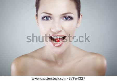 Portrait of young beauty girl eating a candy and holding it in her mouth