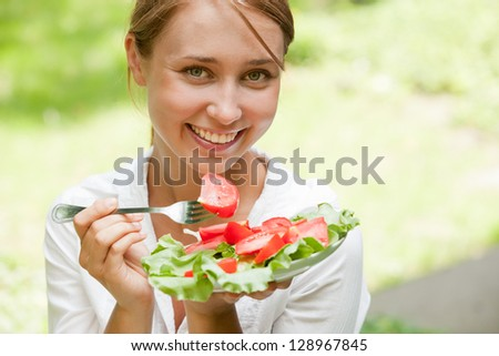Portrait of young beauty woman eating salad