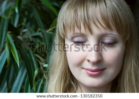 Portrait of young beauty woman with closed eyes on the nature background