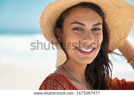 Portrait of young beauty woman with ocean in background and copy space. Beautiful fashion woman at the beach protecting herself from the sun with hat. Close up face of glamour girl with sunhat at sea.