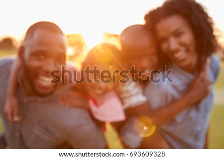 Portrait of young black couple with children on piggyback #693609328