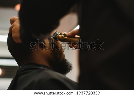 Portrait of young black man being trimmed with professional electric clipper machine in barbershop.Male beauty treatment concept. Young African guy getting new haircut in barber salon Stock photo ©