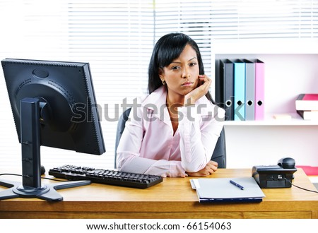 Portrait of young black unhappy business woman at desk in office