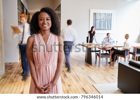 Portrait of young black woman in a busy modern workplace