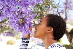 Portrait of young black woman smelling flowers on tree