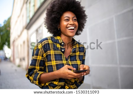 Portrait of young black woman walking on street holding mobile phone stock photo