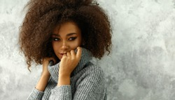 Portrait of young black woman with an afro hair wear high-neck wool and cashmere sweater