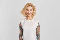 Portrait of young blond girl with tattoos over her hands wearing in whit t-shirt, smiling and showing her teeth to the world. Isolated on white wall