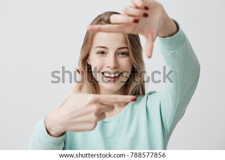 Stock Photo Portrait of young blonde positive female with cheerful expression, dressed in casual light blue sweater, has good mood, gestures actively at camera. Beautiful dark-eyed woman posing indoors