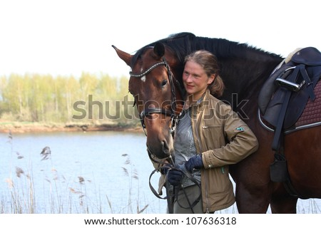 Portrait of young blonde woman and beautiful brown horse on the coast of the river in spring