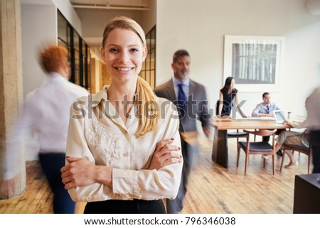 Portrait of young blonde woman in a busy modern workplace