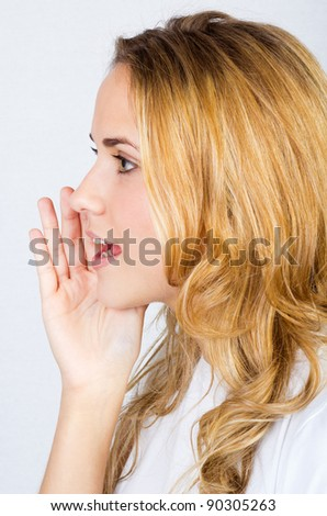 portrait of young blonde woman whispering gossip
