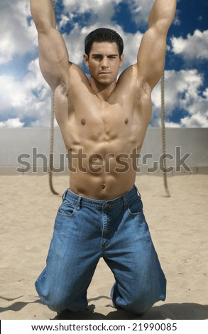 Portrait of young bodybuilder hanging on beach with bright blue sky