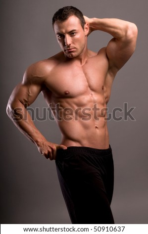Portrait of young bodybuilder man on grey background.