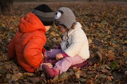 Portrait of young boy and girl sitting on the ground among dry leaves and playing together