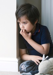 Portrait of young boy biting his finger nails with thinking face,Kid siting with teddy bear and looking out with curiouse face,Childhood and family concept, emotional child, portrait indoor