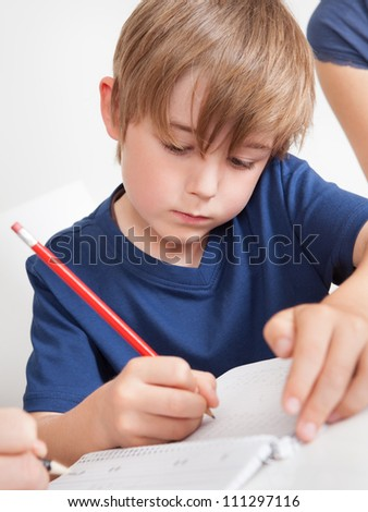 Portrait of young boy doing homework at home