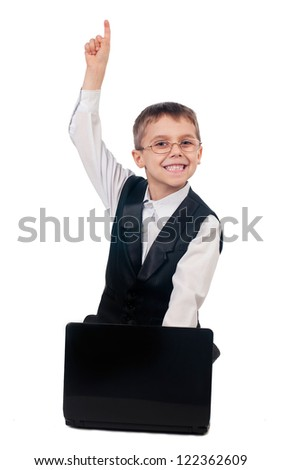 Portrait of young boy dressed up in suit sitting on the floor and working with laptop, isolated on white background
