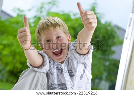Portrait of young boy giving his thumbs up