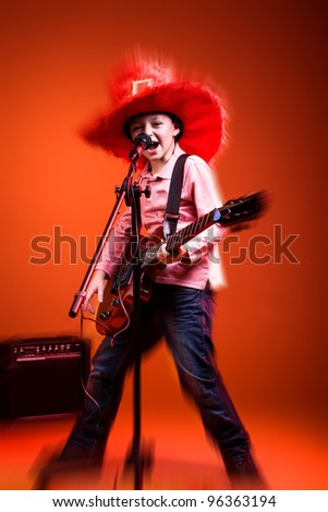 portrait of young boy with a guitar on the stage