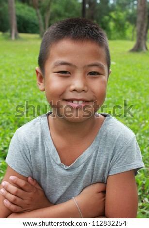 Portrait of young boy with green grass background.