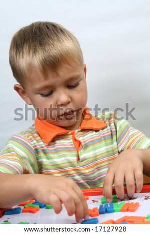 portrait of young boy with magnet letters