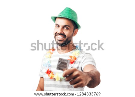 Portrait of young brazilian man wearing carnival costume showing a condom #1284333769