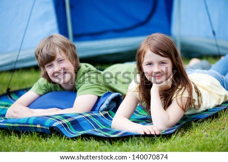 Portrait of young brother and sister lying on blanket with tent in background at forest