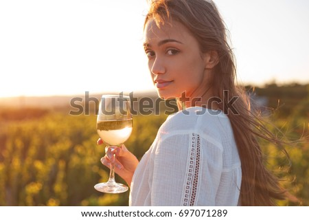 Portrait of young brunette beauty in the vineyards having wine.