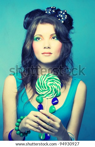 Portrait of young brunette with creative make-up and with lollipop in her hands.