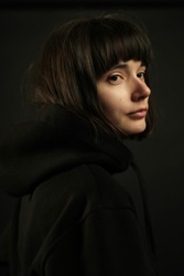 Portrait of young brunette with short hair and bob haircut, without make up, wearing black hoodie, looking over shoulder, isolated on black background