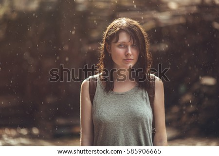 portrait of young brunette woman in the rain, horizontal