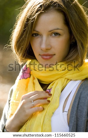 Portrait of young brunette woman in yellow scarf in autumn colors.