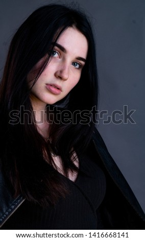 Portrait of young brunette woman sitting on high wooden chair with crossed legs. Fashionable stylish girl wearing wide leg pants. Studio shoot on gray background #1416668141