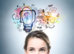 Portrait of young brunette woman smiling, looking upwards at a colourful light bulb on a concrete wall. Concept of new idea, plan