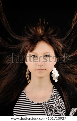 Portrait of young brunette woman, with her hair in motion
