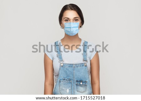 Portrait of young brunette woman with surgical medical mask in denim overalls standing and looking at camera. medical and health care concept. indoor studio shot isolated on gray background.