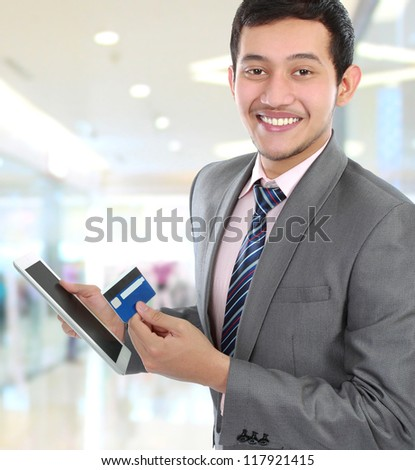 portrait of young business man hold a tab and credit card