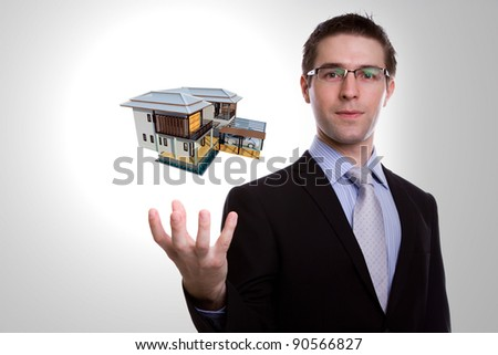 Portrait of young business man holding house