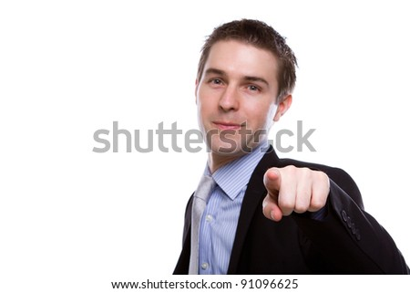 Portrait of young business man in a suit pointing with his finger against white background