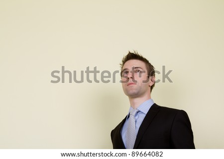 Portrait of  young business man looking up