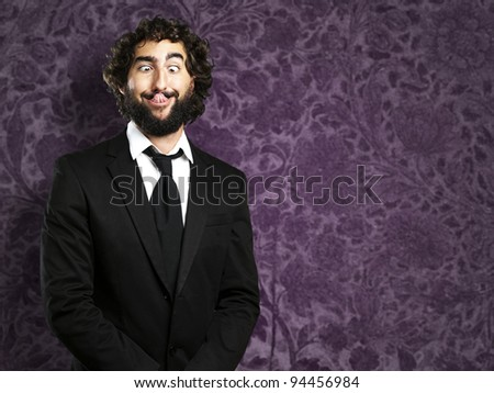 portrait of young business man showing the tongue against a vintage wall