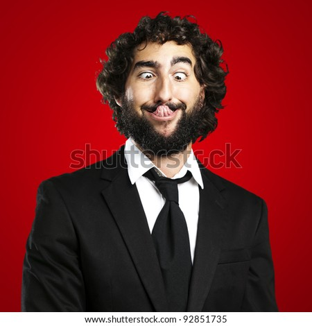 portrait of young business man showing the tongue over red background