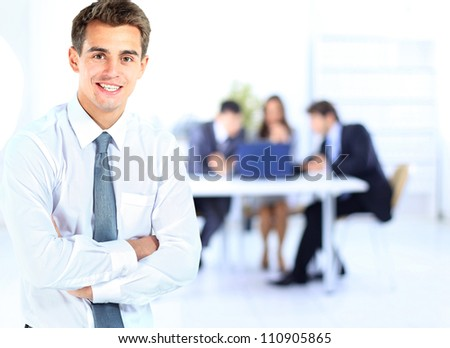 Portrait of young business man smiling with colleagues in background