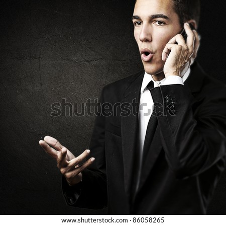 portrait of young business man talking on mobile against a grunge background