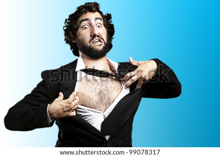 portrait of young business man tearing his suit over blue