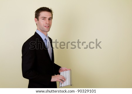 Portrait of young business man using a wireless keyboard for presentation