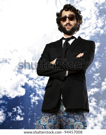 portrait of young business man wearing swimsuit against a cloudy sky background